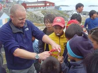 Daz entertains the local children with magic tricks.