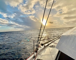 Image from Blown Away, sailing toward a setting sun on calms seas in the Atlantic Ocean.